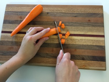 Someone chopping carrots on a cutting board - image