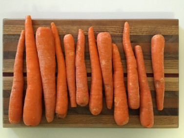 Raw carrots on a cutting board - image