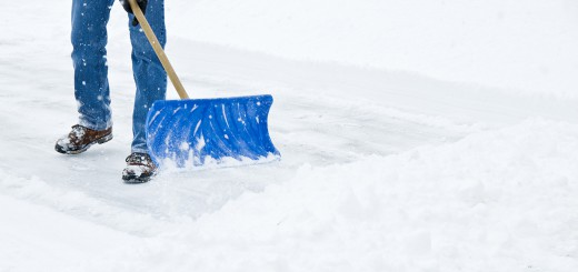 Man shoveling sidewalk with blue shovel