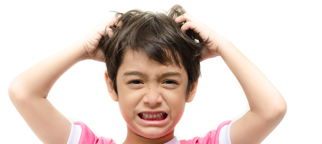 boy with lice scratching his head